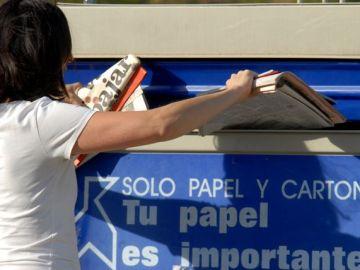 Una persona reciclando papel en el contenedor azul