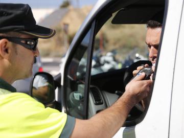 Un agente realiza una prueba de alcoholemia
