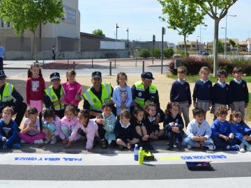 """Escolares pintando el mensaje """"Para, mira y cruza"""" en paso de peatones ubicado en la avenida de la Universidad."""