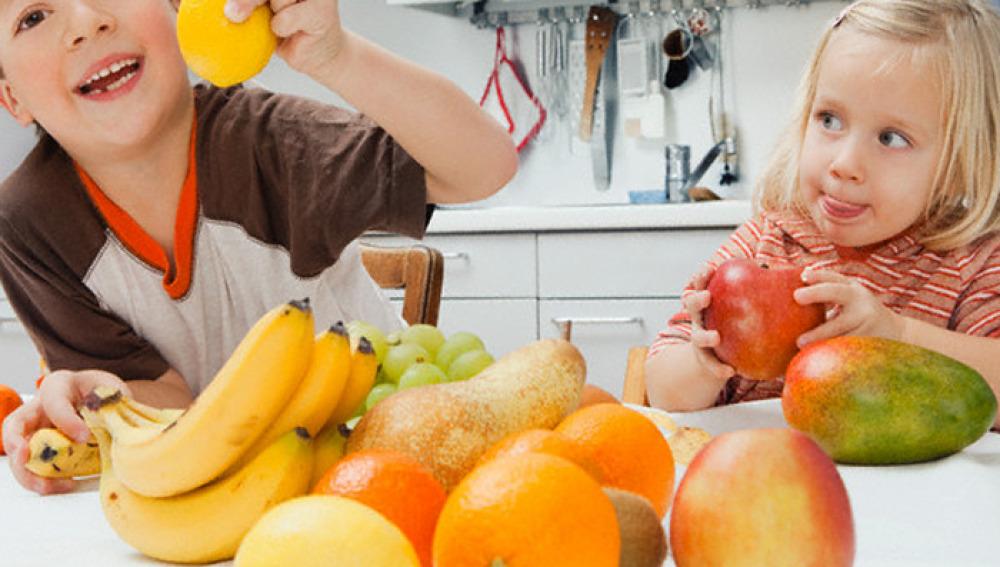 Un niño y una niña con fruta