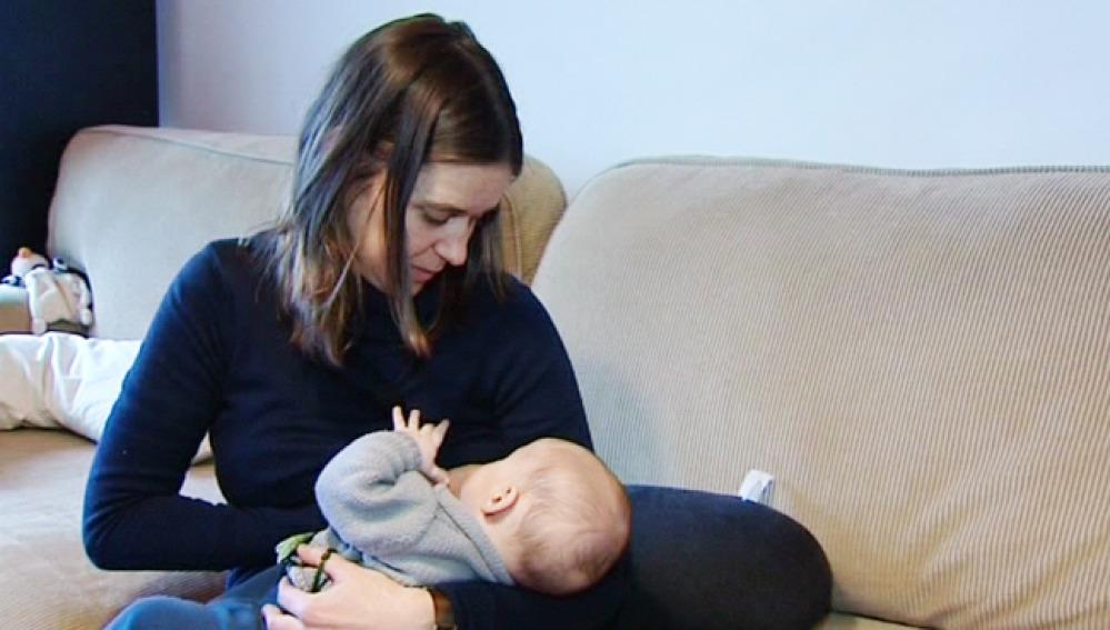 Una mujer da el pecho a su bebé.