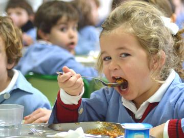 Niña comiendo en un comedor escolar